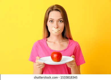 Woman with taped mouth and healthy apple on color background. Diet concept