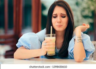 Woman Tasting Sour Lemonade Drink in a Restaurant. Supertaster person reacting to freshly squeezed lemon juice beverage