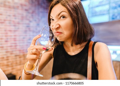 A woman at the tasting tries and smells the aroma of an ugly glass of wine. Concept of alcoholism and spoiled drink