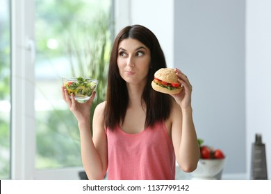 Woman with tasty burger and fresh salad indoors. Choice between healthy and unhealthy food