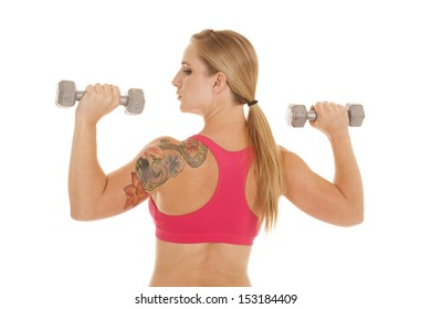 A woman with a tattoo holding weights looking to the side.
