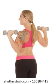 A woman with a tattoo holding up weights looking to the side.