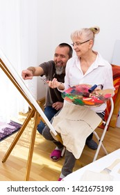 Woman is taught in the art of painting