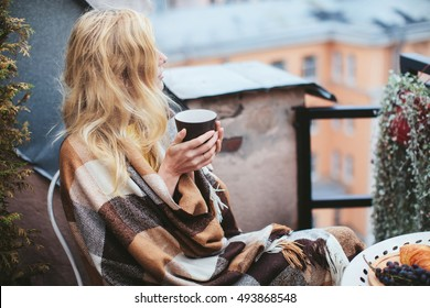 woman with tea sheltered blanket breakfast on the balcony overlooking the city