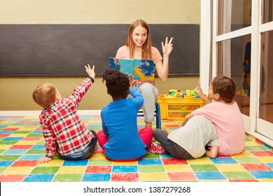 Woman as a teacher and children have fun together while reading aloud in kindergarten or daycare