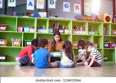 woman teacher in classroom teaching preschool kids, joyful learning together with mixed-race international children