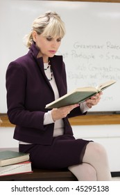 Woman teacher or instructor in a college, university, high school, middle school, elementary classroom sitting on her desk holding a book and reading.