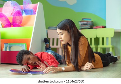 woman teacher try to rise up a preschool as stubborn of boys to pay learning and attention in studying, naughty boys out ot controll in classroom at kindergarten pre school. Uncontrolled behaviour
