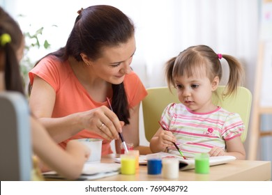 woman teaches children painting at kindergarten or playschool