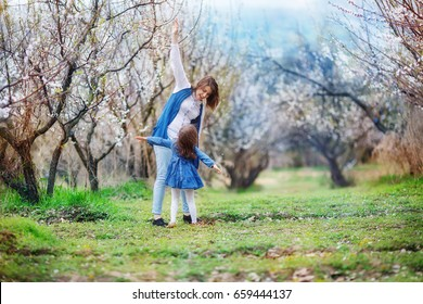 The woman teaches the girl to fly. Mother and daughter stand in the midst of a blooming apricot garden, with arms outstretched