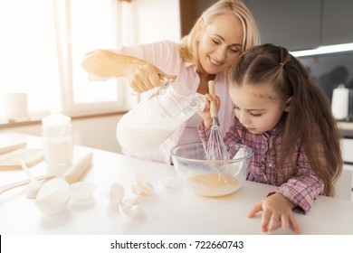 A woman teaches a girl how to cook a homemade cake. The girl whipped the eggs in a glass bowl. A woman pours milk into a glass bowl