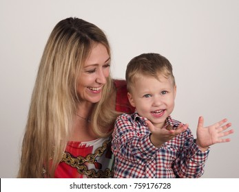The woman teaches grandchild to be generous /boy holds out a candy sitting on his grandmother's lap /boy with candy at his grandmother's hands