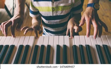 Eine Frau lehrt ihren Sohn, Klavier zu spielen. Der Junge beherrscht das Klaviermusikinstrument. Ein Kind lernt Musik. Die Hände von Kindern und Frauen auf den Klavierschlüsseln. Musikunterricht. Tutor für ein Kind.