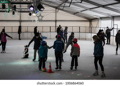 Woman teaching children ice skating during a lesson on circa January 2018 in Poznan, Poland
