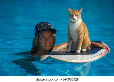 Woman teaching her cat to ride surf in ocean