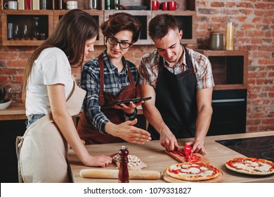 Woman teaching her friends how to cook. Group of people cutting ingredients in kitchen. Cooking class, culinary, friendship, togetherness, food and people concept