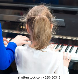 Woman teaching little girl to play the piano. Back view.
