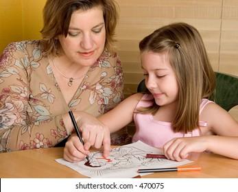 A woman teaching a little girl in Sunday School.