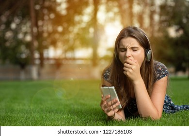 Woman teenager girl yawning bored with on line content holding a mobile phone outdoors lying down on green lawn headphones on head. Multicultural model, mixed race, asian russian girl. Copy space.