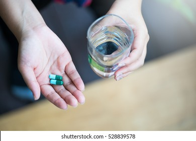 Woman teenager hands with pills and glass of water