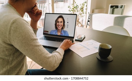 Woman teleconferencing with female colleague on laptop. Colleagues working from home having a video call and discussing work.