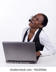 Woman with telephone headset and a laptop, serving a customer telephonically.