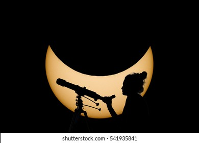 Woman with telescope Safe Solar Eclipse observation. Real Sun in the background. Observing Solar Eclipse through a telescope and a special filter to reduce sunlight.