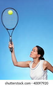 A woman tennis player serving against a blue background.