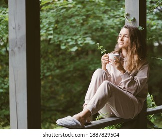 Woman in terrace with cup of coffee. Green yard. Woman in soft light  costume. Summer relaxing lifestyle. Village lifestyle.