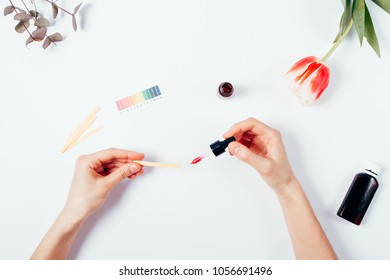 Woman testing cosmetics by using litmus paper. Top view of female hands on white background, applying with a pipette serum into a litmus test paper. Determination of pH level in cosmetics