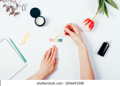 Woman testing cosmetics by using litmus paper and scale. Top view of female hands measuring of pH level in cosmetics among tulip, eucalyptus branch and notepad with pencil on white background