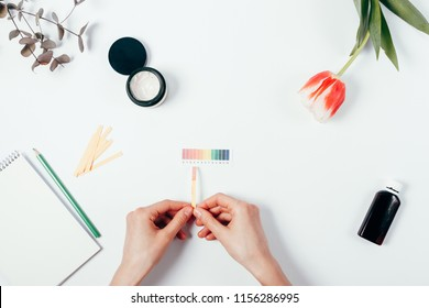 Woman testing cosmetics pH level by using litmus paper and color scale. Top view of female hand matching reaction color on white background.