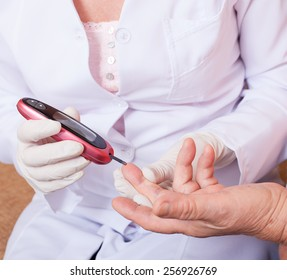 Woman testing for high blood sugar. Woman holding device for measuring blood sugar