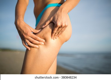 Woman is testing the skin for stretch marks and cellulite on the beach.Woman holding/showing cellulite area.Self consciousness,self confidence and body insecurity.Summer beach body.Cellulite removal