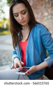 Woman texting. Closeup young happy smiling cheerful beautiful woman girl looking at mobile cell phone reading sending sms isolated cityscape outdoor background.