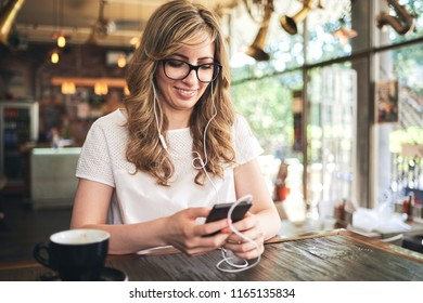 Woman texting and listening music on the mobile phone in the cafe