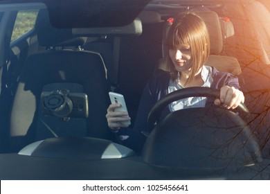 Woman texting on her mobile phone while driving. Dangerous driver.