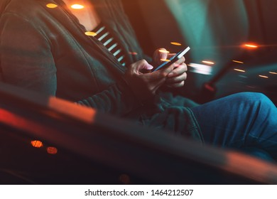 Woman texting on mobile phone in car at night on a parking lot, adult female person using smartphone for communication, selective focus