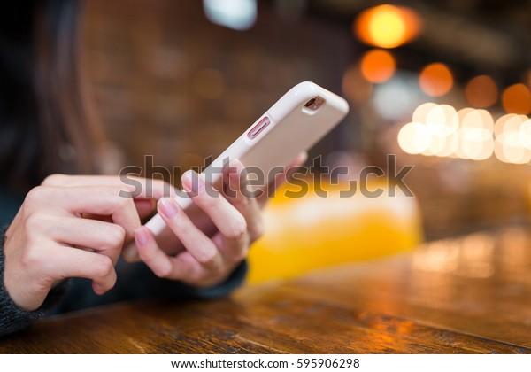 喫茶店で携帯電話でメールを送る女性