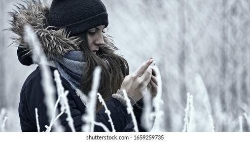 Frauen schreiben SMS auf Smartphone. Vielleicht schreibt sie Nachrichten, SMS, MMS, Pfosten, teilt ihre Gefühle oder Gedanken. Sie ist im Winter morgens draußen.