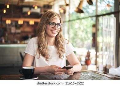 Woman texting over mobile phone in the cafe
