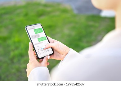 Woman texting with phone outdoors. Text message with smartphone. Digital sms and instant messaging chat. Person using cellphone in park outside in summer. Conversation with boyfriend or friend.