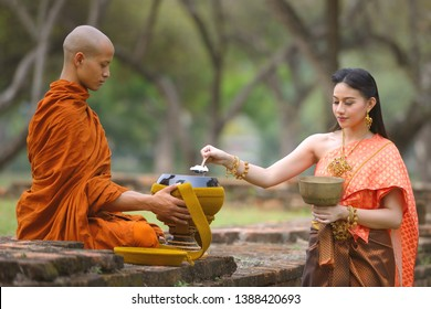 Woman in Thai traditional dress giving food in the bowls of Buddhist monk at Wat Phra Si Sanphet in the early morning, Ayutthaya, Thailand.
