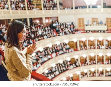 A woman in the theater watches the performance