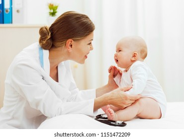 Woman therapist holding baby girl in her office. General medical examination.