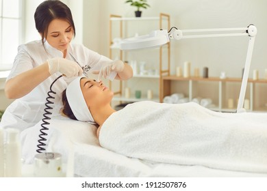 Woman therapist making procedure of oxygen therapy or jet peeling with special apparatus equipment for young woman in beauty spa salon, side view. Oxygen therapy in cosmetology
