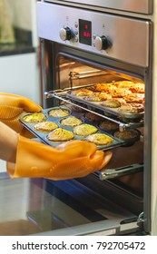 Woman with thermos gloves putting the muffins back in the oven