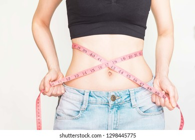woman with thin waist,tightened up, and pink measuring tape Waistline,used a measuring tape around her waist,Conception about health care