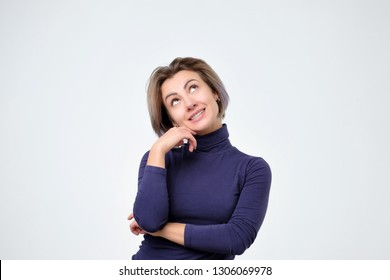 Woman thinking about thing she desire with intrigued and interested expression