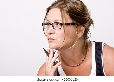 Woman thinking or listening. She is focused with a pencil in her hand